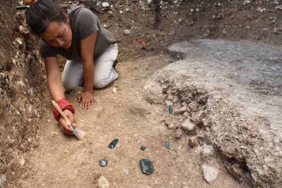 Melina Garcia excavating Cache NR3 (900-800 BC) with greenstone axes and a perforator at Aguada Fénix. Credit Takeshi Inomata