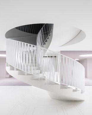 Royal Museum of Fine Arts, Anversa by KAAN Architecten. The circular staircase seen from the ground floor, the mosaic on the floor is a contemporary interpretation of the original one located in the entrance hall, right above © Stijn Bollaert